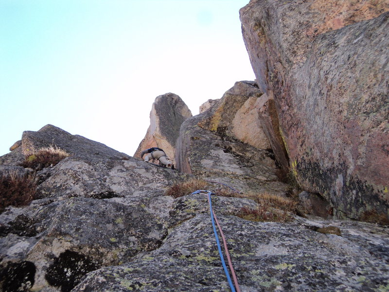 Joe approaches to top of the left-facing dihedral on P6.  The spacious belay is to the right of the pinnacle on the skyline.