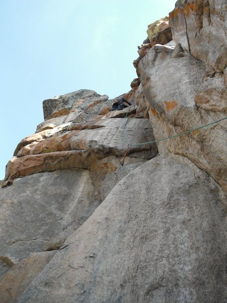 Ready to make exit move after the lasso horn, a key horizontal placement is shown on left face below the climber.