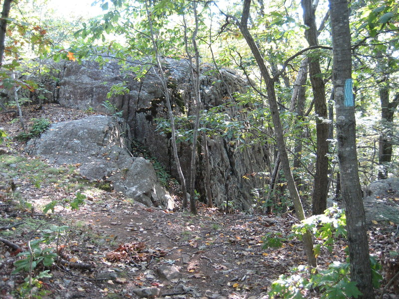 Hiking south, the Metacomet trail goes up over the top of the crag. Descend right for crag base.