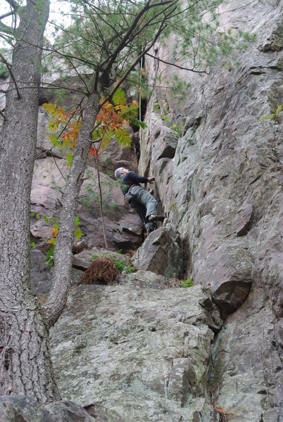 "Erol Altay climbing the starting moves of ""Coup de Gras"" just off the big ledge at crag 1/2 height."