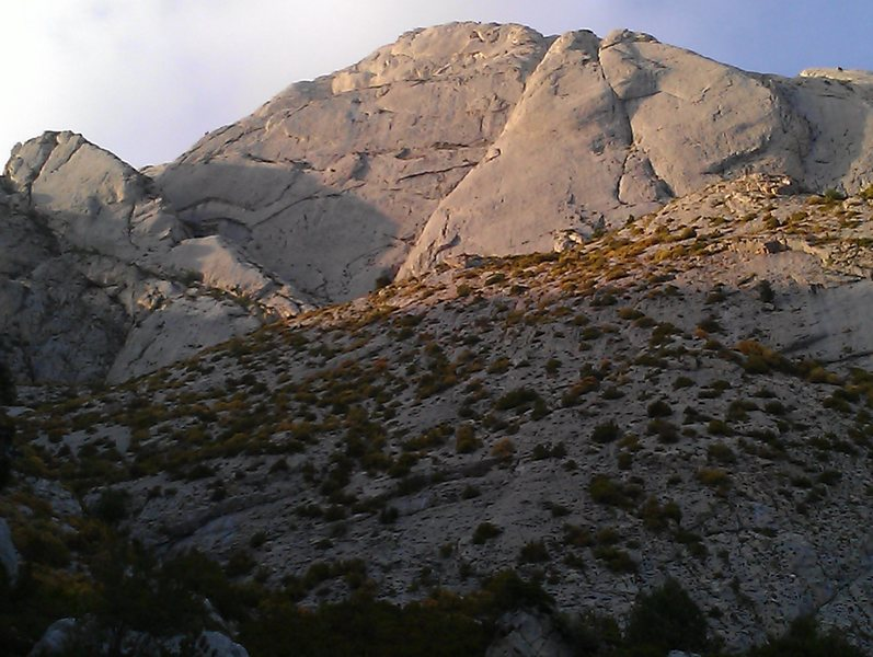 This is a photo of Pedraforca's 500m south face, the Pollego Inferior. Via de Tots climbs up left side. Some take the huge ramp (Diagonal) up and left to omit the first few pitches.