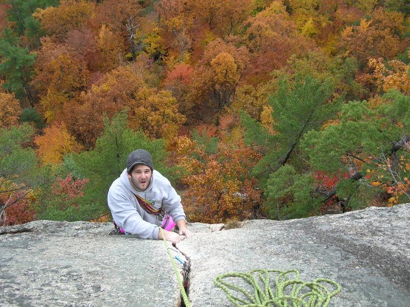 Joshua nearing the tree belay ledge atop Inferno's crack pitch.