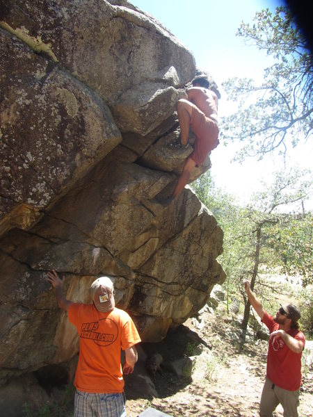 Going for the top out on the V1 problem in the center of the boulder