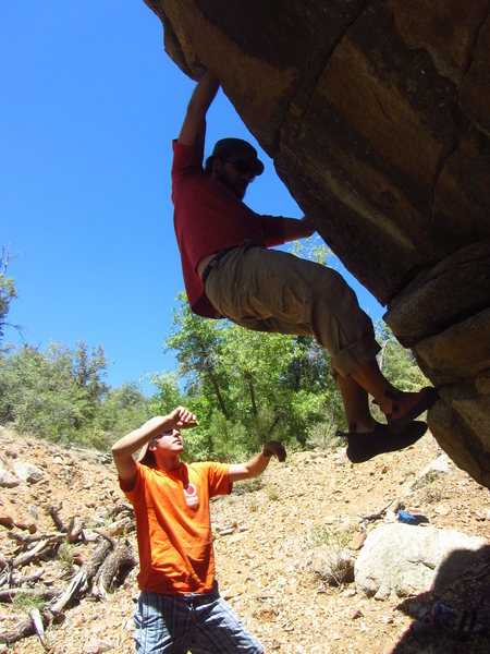 Luke Bollinger on the starting moves of the overhanging problem in the center of the boulder.