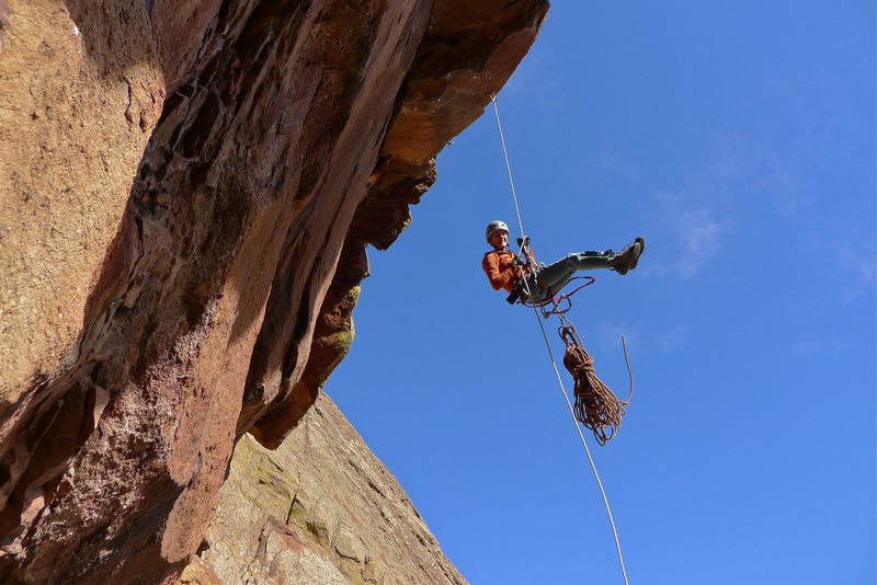 Heather Weidner rapping over the crux roof for another work session on the 13c pitch.