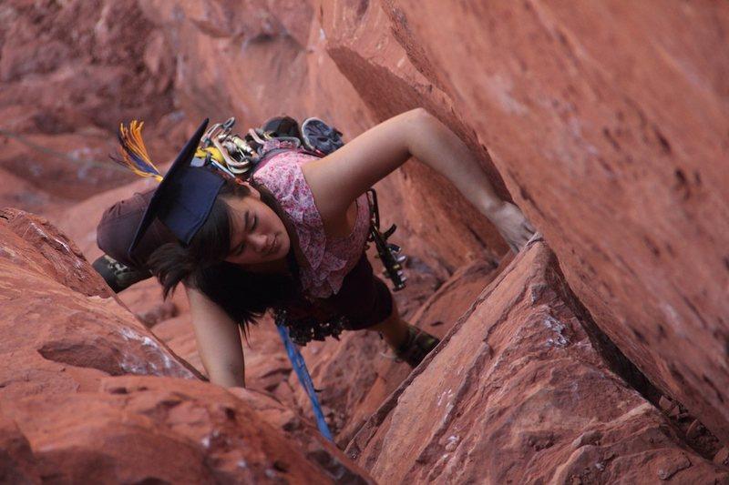 Sarah climbing pitch one in graduation garb