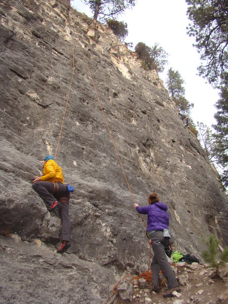 Climber in yellow jacket is top roping Jack Rabbit.<br> <br> The Bunny Slope, Sunshine Wall.<br> Spearfish Canyon, SD.