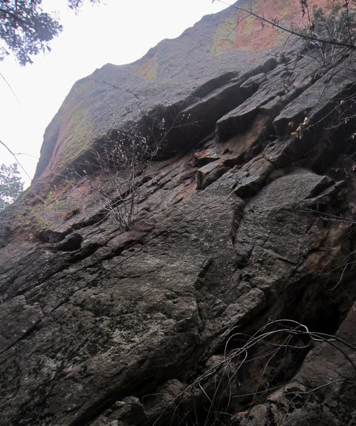 The North Buttress (5.10+, PG13) ascends the two sickle-shaped flakes low and right on the image to reach the sloping ledge, then ascends to the hand-to-tips crack through the 4-foot roof and then out diagonally left to the ridge line.