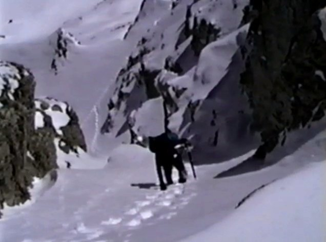 Old VHS screen capture of John Fujii coming up the right branch of Red Slate North Couloir, in winter conditions.