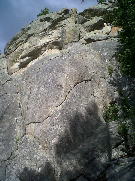 Rock Lobster climbs the indistinct dihedral/gully on the left for 15 feet, then moves right to a bolt by a seam that is followed up and right to a blonde undercling in the upper part of photo. (I'm not talking about the long undercling that goes right and up, across the middle of the photo.) From the right end of the high, short undercling, climb up through a lichen-infested break to the rim. Build an anchor. Walk off.