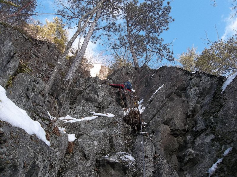 This is the upper start to Wendell's Dike' (winter ascent). The dike begins after the large pine trees above this crag band. Ryan Barber is approaching the pin. There are three ways up it and two share the same pin. The third is right of the pin and misses using it.