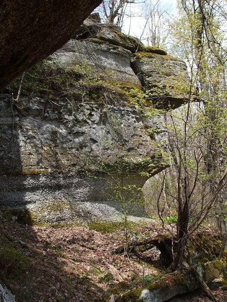 View of the formation from the approach, the route starts from underneath the overhang and follows features up the far side.
