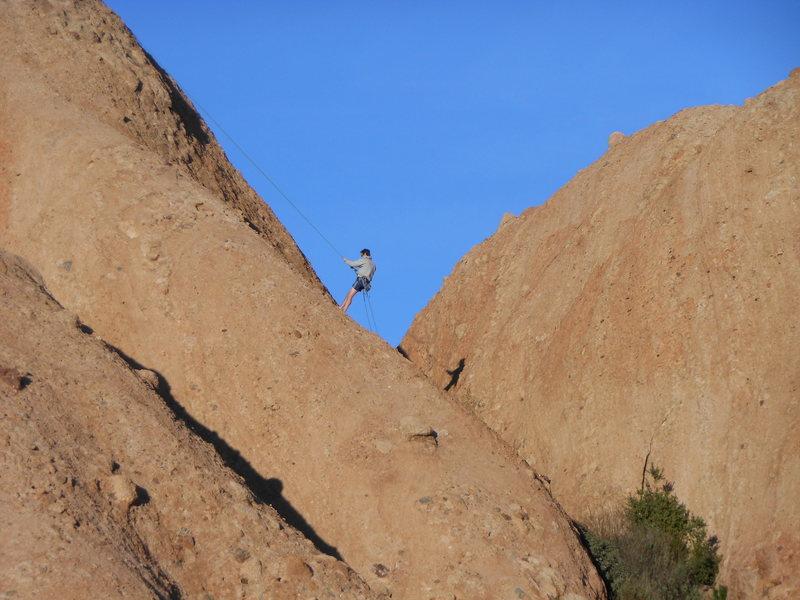 "A climber rappelling off ""Cracker Jacks."""