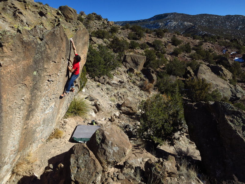 Big move to the top of the boulder, photo by Greg Crum