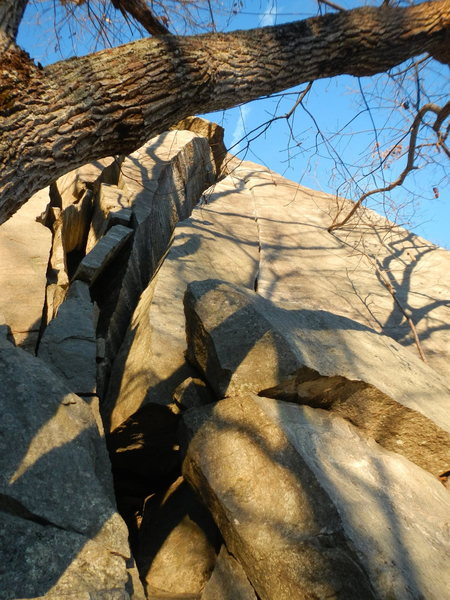 It is the crack to the right of the larger chimney starting right on top of the boulders, belay from the top of the boulders.