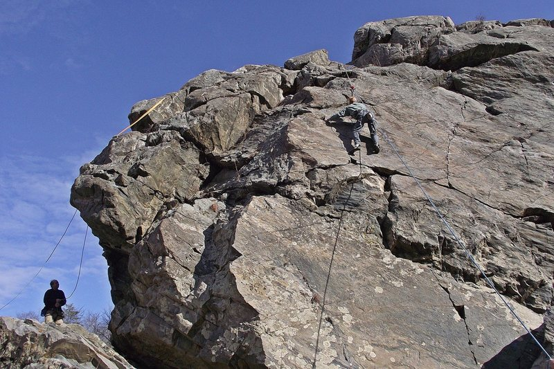 The Purple Horse crag viewed from the river.  Rob Whitestone working one of the medium hard face options.  Others include the face route of the right ridge line, and the blankish one just to the climber's right.  Further right it gets easier.<br> <br> John Ely is just roping up for Barn Roof.<br> Photo: Dave Rockwell