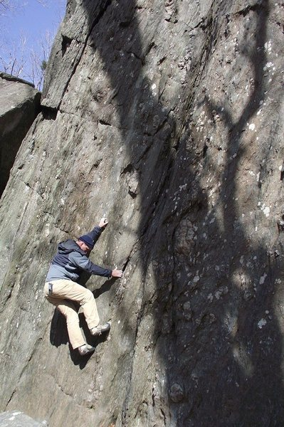 A boulderer has his left hand on the crystal making the plumb line of Shipley's.  Photo: Dave Rockwell