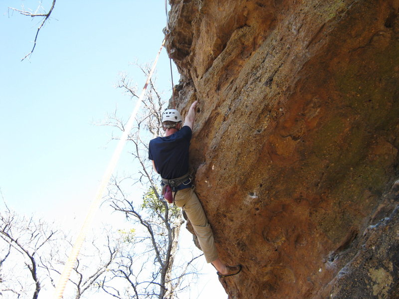 Climber on Unprepared 11-, pulling over the roof bulge. Climbed from below right where chalked holds are seen.