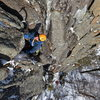 Cysty Ugler: A climber moves onto the ledge at two-thirds height.