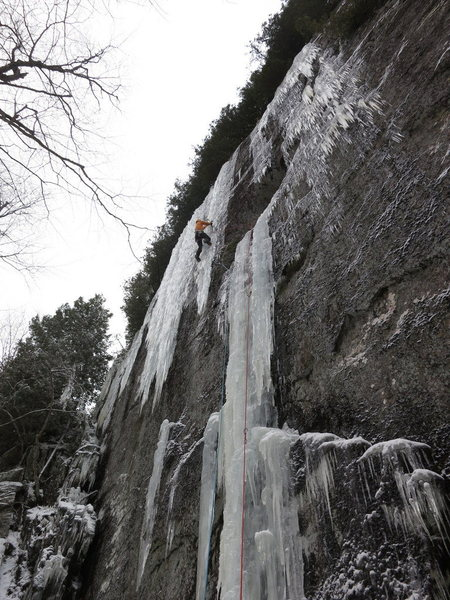 Climber on the upper curtain of Ice Storm. This photo shows how the route formed in 2013; usually one has to traverse further left to the bigger curtain.