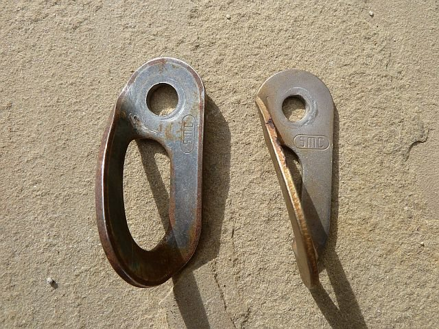 New (left) and old (right) style SMC bolt hangers. Note the stamp is oriented differently on the two styles.