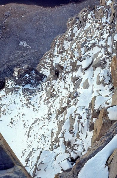 1971 Hammerless FA North Face. Looking down the snow and ice covered ledges, my footprints are visible descending to the point where I unroped above the 5th class pitches, and began free soloing the remainder of the route.