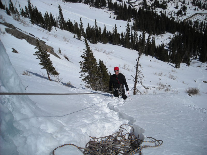 Steve Duff atop 1st pitch of scottish gully. Observe slide zones above the band of trees!