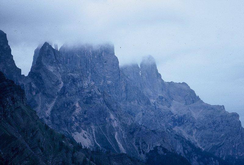 Cima della Madonna and Sass Maor, wreathed in clouds. Telephoto from San Martino di Castrozza.
