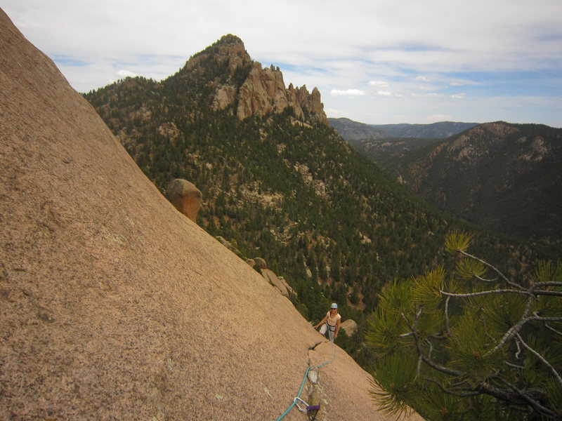Kat A. following the traverse at the end of P3 on Bishop's Jaggers (5.9) on The Dome in the S. Platte.  The Cynical Pinnacle lies in the background.