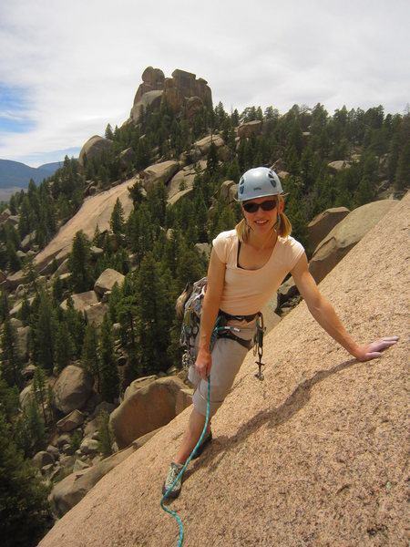 Kat A. lounging at the end of P2 on Bishop's Jaggers (5.9) on The Dome in the S. Platte.  The Bishop formation lies in the background.