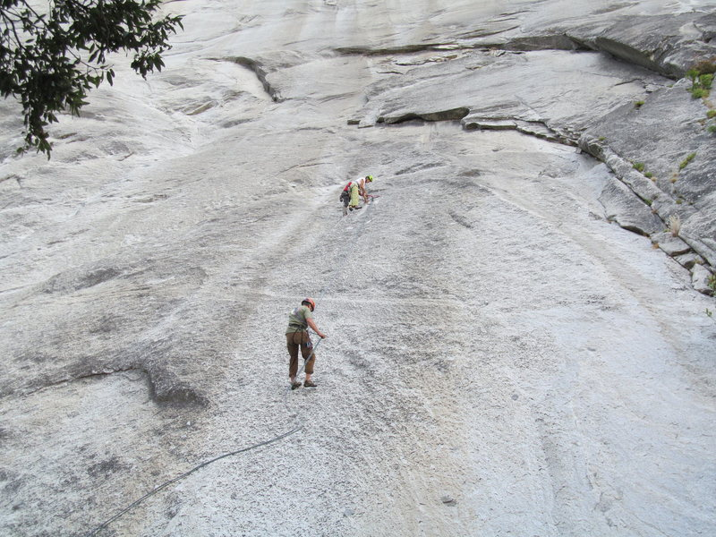 Upper climber is at the first (intermediate) anchor, and the person abseiling is directly over the route's first pitch.