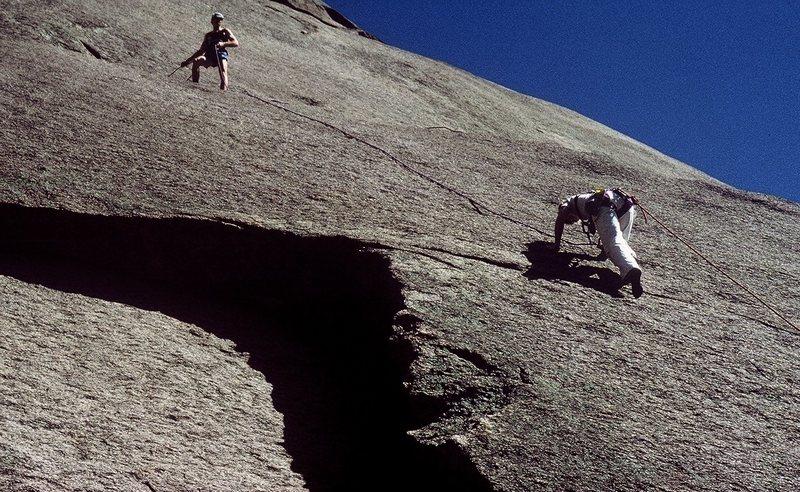 Anne climbing and Gary belaying.