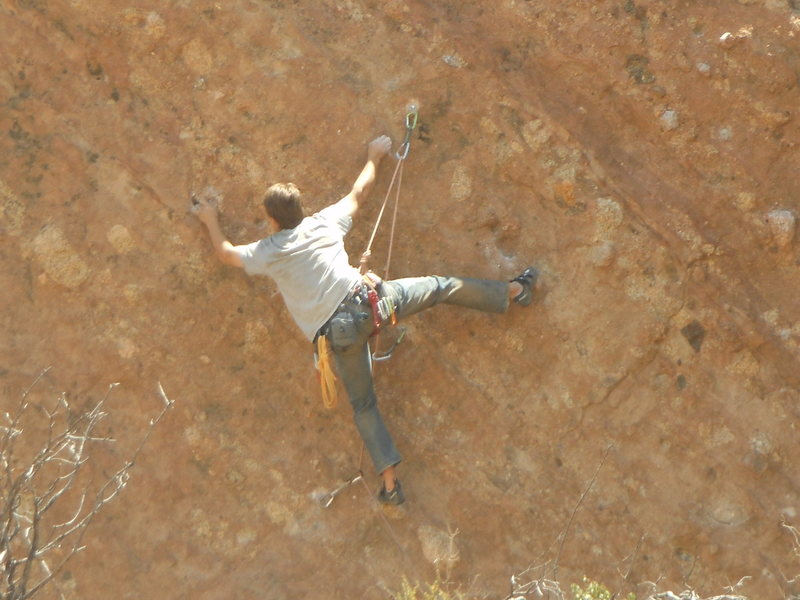 A climber working the moves of a 5.11+ route on the east side of the north end of Corvus Crack.