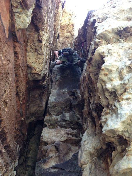 Climb through the chockstone, up the pictured chimney, and look out to the left for a 2 bolt anchor. Follow the bolts to reach the cave pitch