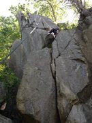Katie climbing through the ledge system just below the top finger crack