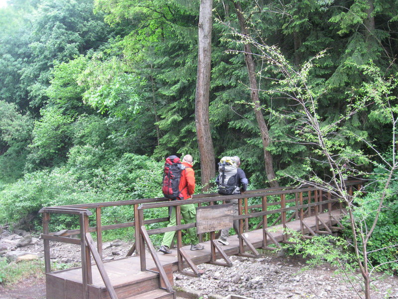 Marin & Dimitri crossing the wooden footbridge by the Belidie Inn parking area to access the crags.