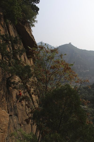 A climber just to the right of &quot;Balance.&quot; The route starts on the big, flat face (more obvious when standing underneath it). to the climber's right. <br> <br> If you look closely in the distance, you can also see one of the older sections of the Great Wall of China!