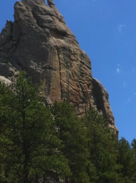 """Snakebite Evangelist from the road. Route follows the prominent left leaning """"crack"""" through tan rock."""
