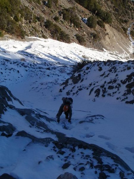 Ty low on the face during early winter. Postholing with some water ice over some low angle boulders.