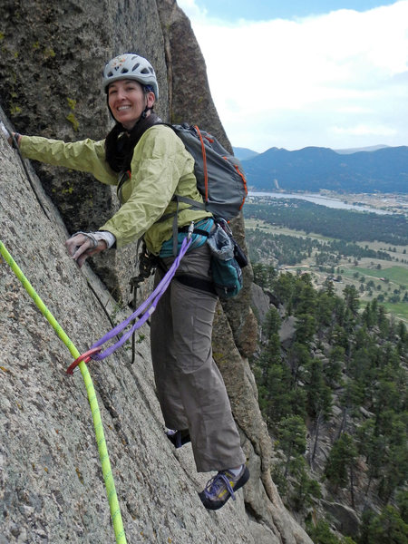 Tori left the belay ledge (at the top of P3) and traversed climber's right to gain the crack for P4. Lake Estes is in the background.