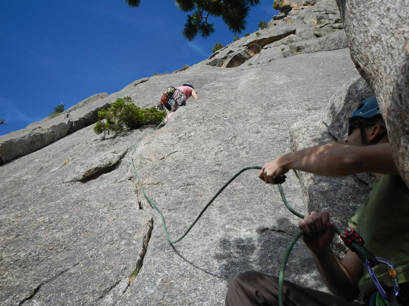 Belayer, Ben, at the top of P1, with the climber, Kate, heading out on P2.