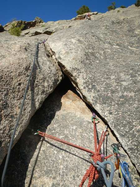 Belay anchor at the top of P2, with Kate heading up P3 to the tree belay, walk-off ledge.