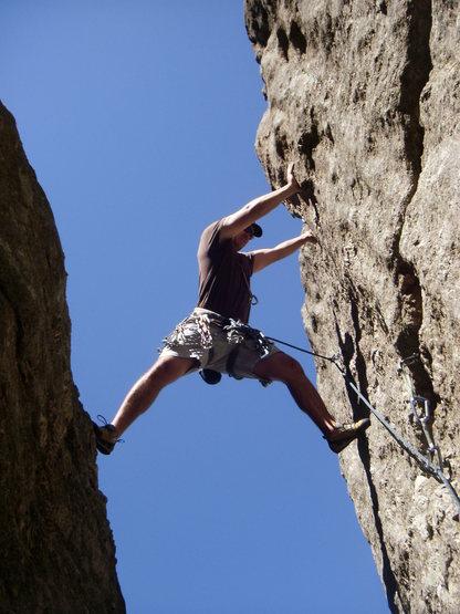 Climber stemming around first bolt