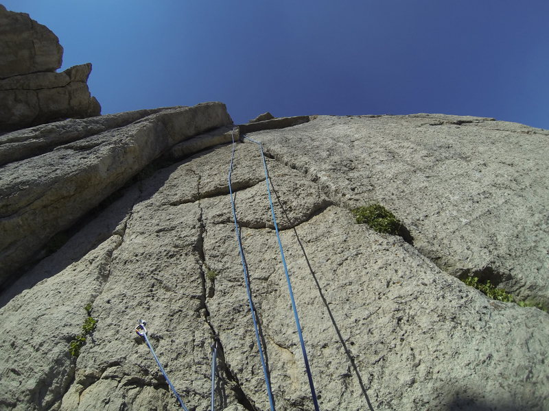 Looking up the route from the belay ledge.  The belay ledge is large and flat but there is one bolt and a piton you can anchor on as well.