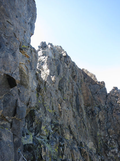 Once you reach the top you climb around the right of the summit pinnacles. It's still another couple/three pitches of scrambling from here and easily soloed or simul'd.