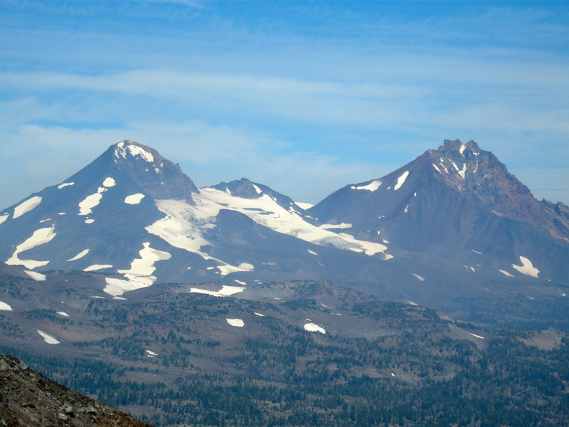 North Sister is on the right. Middle Sister is on the left. The bump to the right of Middle Sister is Prouty Peak.  Photo taken from the saddle of Broken Top, mid August, 2013. Hayden Glacier seen just to the right of Middle Sister.