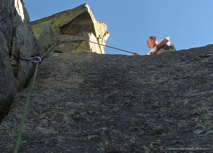 The dicey step-around to a spacious belay.