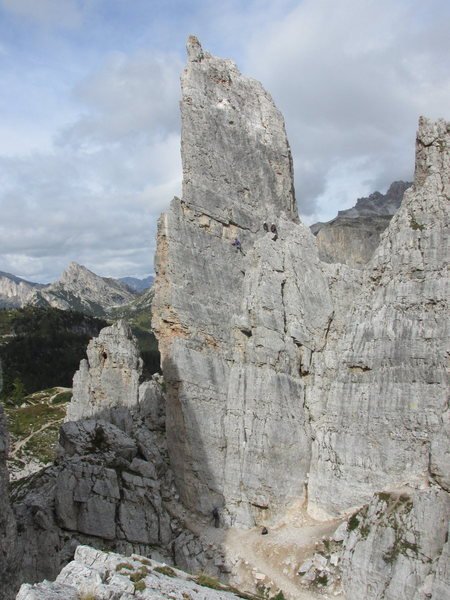 Torre Inglesi and climbers; one stands at the start of the route.