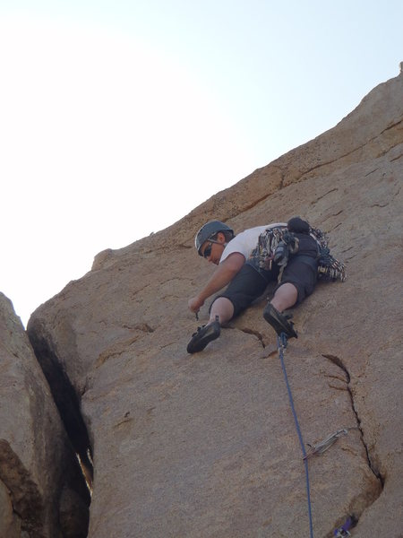 Placing the final pro on the crux pitch.