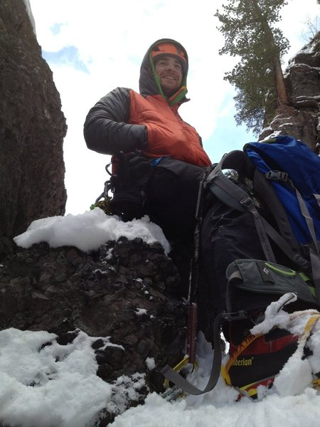 Grover Price sitting on the rock bollard belay. Top of pitch two.